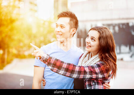Romantic interracial young couple standing together pointing outside in sunset light with intentional lens flare - Stock Photo
