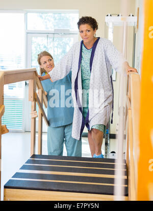 Female Patient Being Assisted By Physical Therapist - Stock Photo