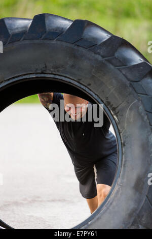 Athlete Lifting Large Tractor Tire On Street - Stock Photo