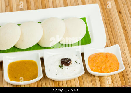 Traditional south Indian breakfast of Idly (Idli) served with condiments (tomato chutney, coconut chutney and sambar) - Stock Photo