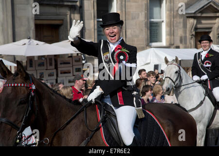 A woman on a horse waving to people in the crowd on the Royal Mile, Edinburgh before the annual Riding of the Marches - Stock Photo