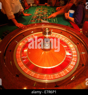 Gambling at the roulette table with chips and spinning wheel - Stock Photo