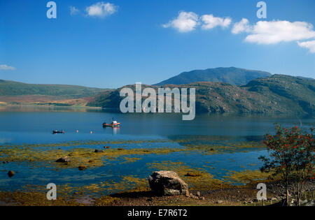 Fishermen in small rowboat and lone fishing boat anchored in Lock Broom along the West Coast of Scotland - Stock Photo