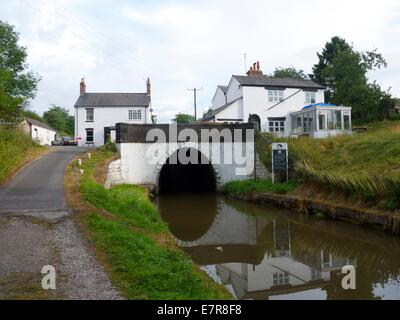 Entrance to a tunnel on a canal with houses on top - Stock Photo