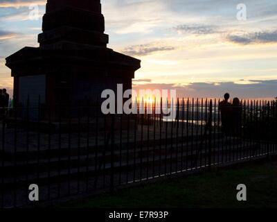 Monument and people in silhouette on top of a hill with the sun setting in the background - Stock Photo