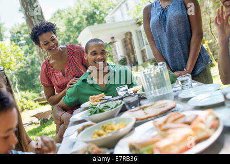 A family gathering, men, women and children around a table in a garden in summer. - Stock Photo