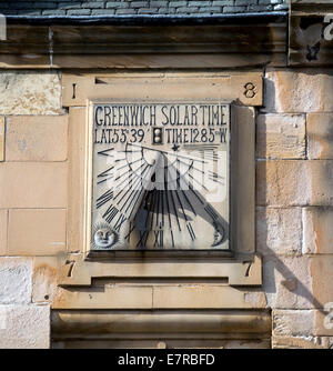 This unusual 1877 Greenwich solar time piece is built into a wall in the main street in Peebles, Scotland. - Stock Photo