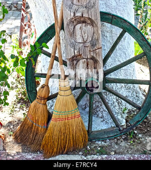 Straw broom with wooden wheel - Stock Photo