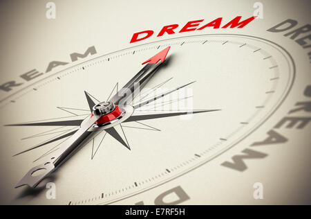 Compass with red needle pointing the word dream, beige paper background, symbol of achieving dreams - Stock Photo