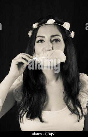 Romantic looking woman with a tiara holding a white feather in front of her mouth - Stock Photo