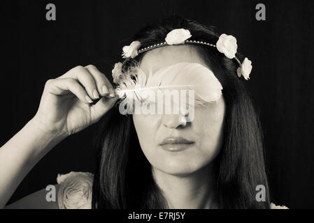 Romantic looking woman with a tiara holding a white feather in front of her eyes - Stock Photo