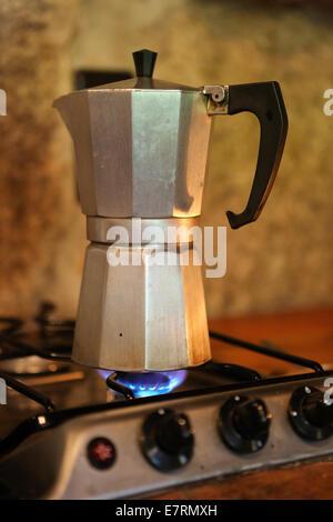 Moka pot brewing coffee on a stove - Stock Photo