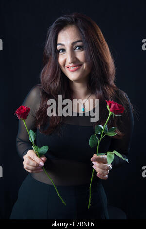 Beautiful brunette woman holding one rose in each hand - Stock Photo