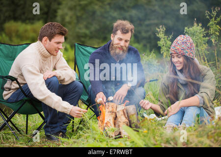 group of smiling friends sitting around bonfire - Stock Photo