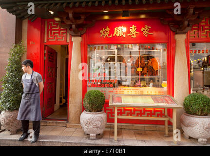 A waiter standing outside his Chinese restaurant, Gerrard St, Chinatown, London UK - Stock Photo