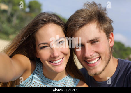 Couple photographing a selfie with the smart phone or digital camera outdoors in the mountain - Stock Photo