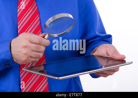 Businessman with red tie and blue shirt holding magnifying glass to screen of tablet, isolated on white background. - Stock Photo