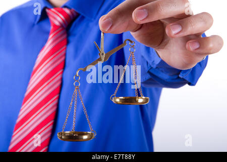 Businessman with red tie and blue shirt holding golden scales unbalanced, isolated on white background. - Stock Photo