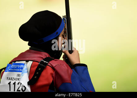 Incheon, South Korea. 24th Sep, 2014. Farzadkhah Dina of Iran competes during the 50m rifle prone women's competition - Stock Photo
