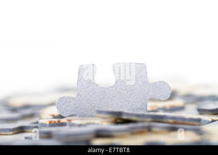 Small puzzle piece standing out among others, isolated on white background. - Stock Photo