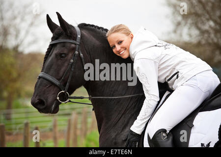 Friesian or Frisian horse, stallion, English bridle, with female rider on horseback - Stock Photo