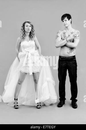 Wedding picture, a bride in a short dress and a bare chested groom with tattoos, holding a cigarette - Stock Photo