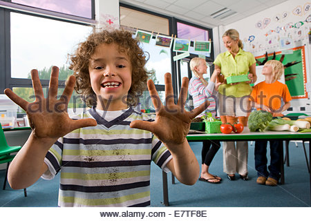 Smiling boy studying biology in classroom showing dirty hands - Stock Photo
