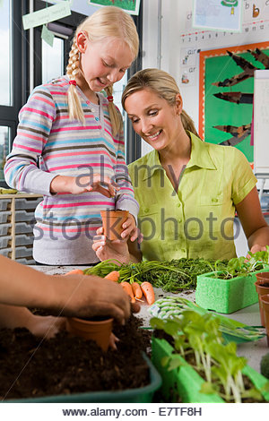 Teacher and students planting vegetables in classroom - Stock Photo
