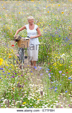 Woman pushing bicycle on path through wildflowers in field - Stock Photo