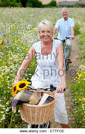 Smiling senior couple riding bicycles on path through field of wildflowers - Stock Photo