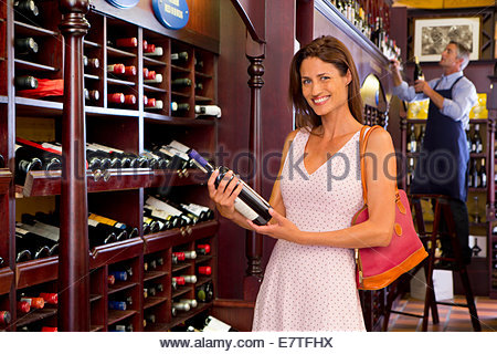 Smiling woman holding bottle in wine shop - Stock Photo