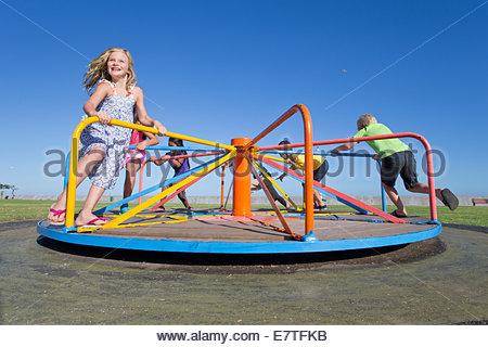 Smiling children riding carousel in park - Stock Photo