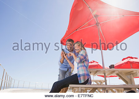 Smiling couple using cell phone under umbrella at waterfront table - Stock Photo