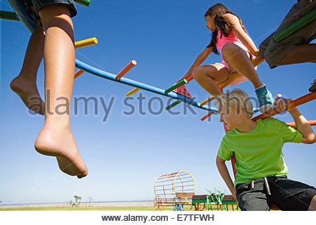 Children sitting on monkey bars at playground - Stock Photo