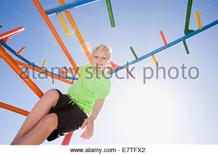 Smiling boy playing on monkey bars at playground - Stock Photo