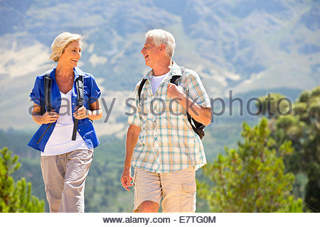 Older couple hiking on rural hillside - Stock Photo