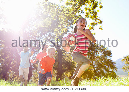 Grandparents and grandchildren running with ball in rural field - Stock Photo