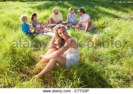 Multi-generation family having picnic in rural field - Stock Photo