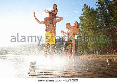 Water splashing on family on wooden dock at lake - Stock Photo
