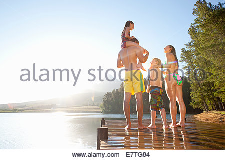 Family standing on wooden dock at lake - Stock Photo