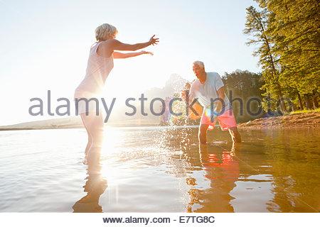 Older couple splashing each other in lake - Stock Photo
