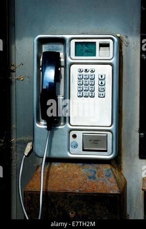 A public telephone inside a BT phone booth england uk - Stock Photo