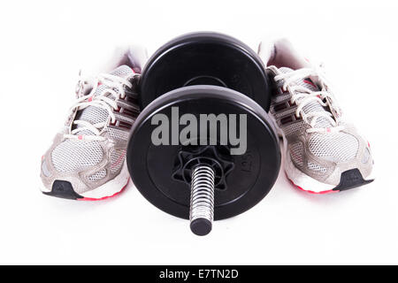 Black gym barbell, dumbbell with disks and sport shoes, isolated on white background. - Stock Photo