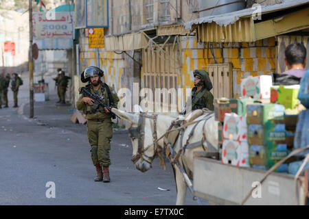 Hebron. 23 Sept, 2014. Israeli soldiers block the road in front of Palestinians during clashes at the center of - Stock Photo
