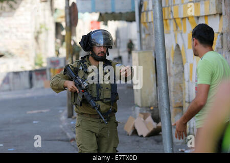 Hebron. 23 Sept, 2014. Israeli soldier blocks the road in front of Palestinians during clashes at the center of - Stock Photo