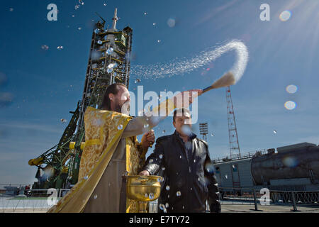 A Russian Orthodox priest blesses the Soyuz rocket on the launch pad at the Baikonur Cosmodrome September 24, 2014 - Stock Photo
