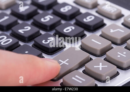Finger pressing plus button of calculator.