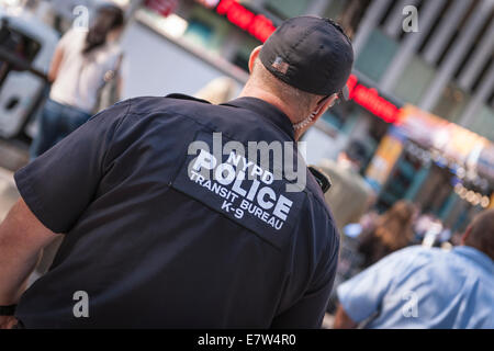 An officer of the NYPD  Police Transit Bureau K9 patrolling Times Square in Midtown Manhattan, New York - USA - Stock Photo