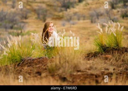 Teenager sits in field of bents - Stock Photo