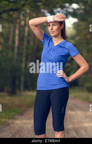 Woman athlete wiping sweat from her forehead onto her wristband as she pauses during her training exercises on a - Stock Photo